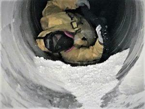 Technician wearing PPE vacuuming duct