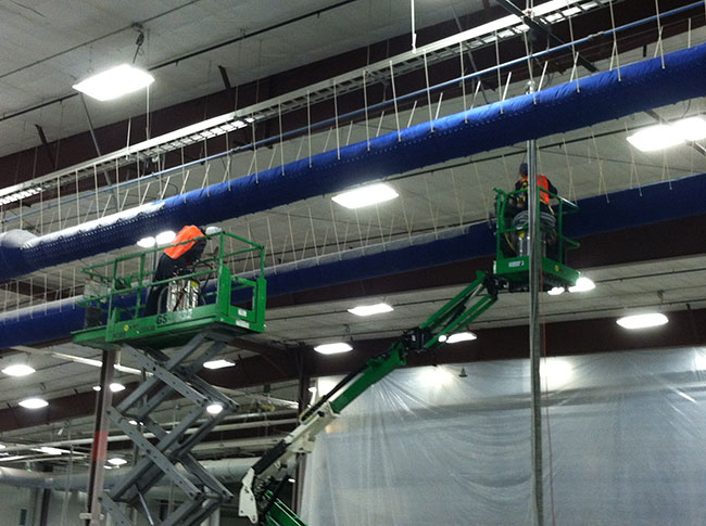 Service-Tech workers removing combustible dust from the interior of an industrial facility